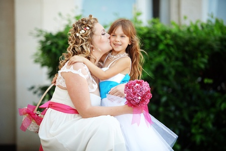 Bride kissing flower girl at wedding photo