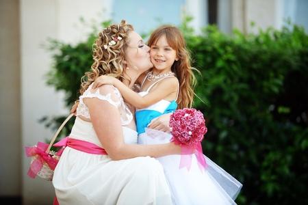 Bride kissing flower girl at wedding photo