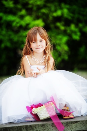 princess dress: Lovely little bridesmaid sitting outdoors at wedding
