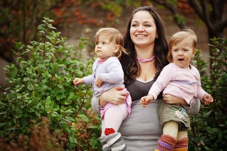 niñas gemelas: Retrato de la madre joven con sus pequeños gemelos