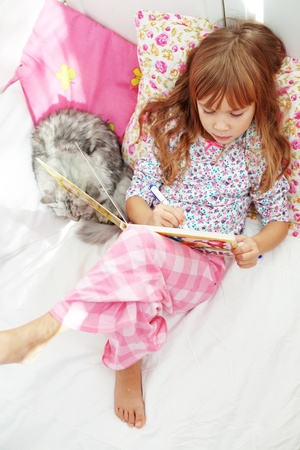 Portrait of child resting in bed with lovely pet photo