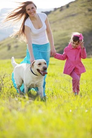 ni�os caminando: Familia feliz caminando con el perro en campo verde Foto de archivo
