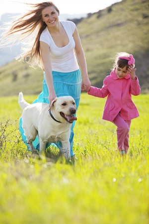 dog walking: Happy family walking with dog in green field