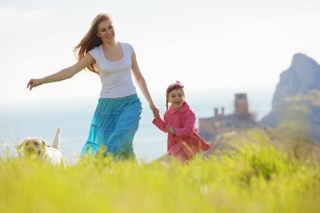 Familia feliz caminar con el perro en el campo verde