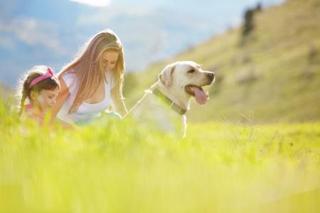 femme et chien: Famille heureuse de marche avec le chien dans le champ vert Banque d'images