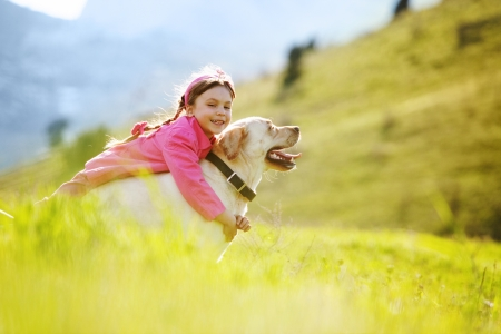 playing field: Happy child playing with dog in green field