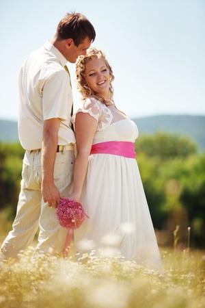 Wedding couple walking outdoor in field photo
