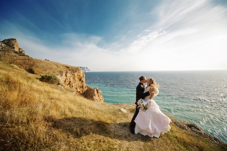 Kissing wedding couple staying over beautiful landscape Stock Photo