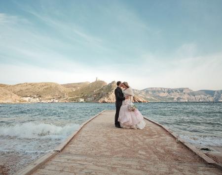 Kissing wedding couple staying over beautiful landscape photo