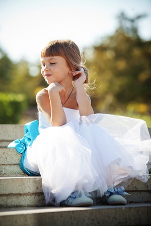 Lovely little bridesmaid sitting outdoors at wedding photo