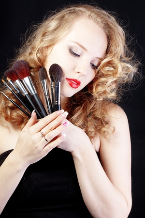 Portrait of beautiful make-up artist isolated on black background photo