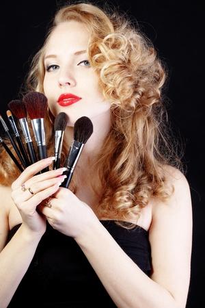 visagist: Portrait of beautiful make-up artist isolated on black background