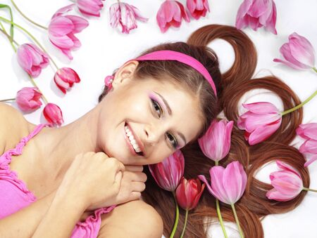 Portrait of lying beautiful wellbeing girl with sparse tulips Stock Photo - 12935093
