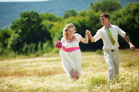 Wedding couple walking outdoor in field photo