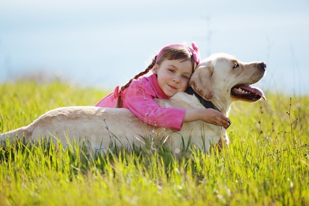 Happy child playing with dog in green field photo