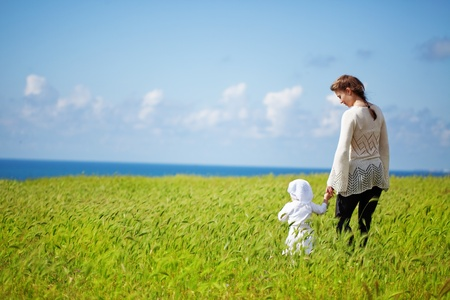 Mother walking with her baby in spring green field photo