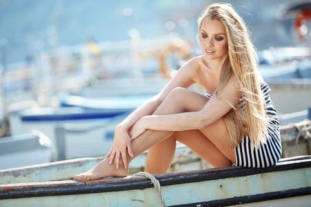 Beautiful sexy woman wearing sailor striped dress posing in boat photo