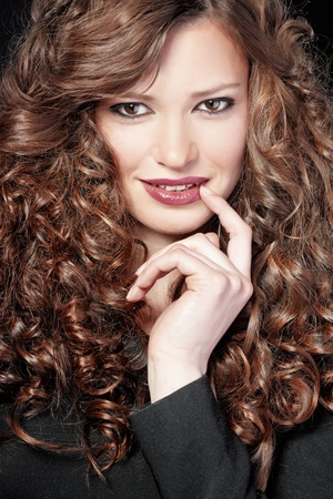 Portrait of young beautiful woman with long curly volume hair photo