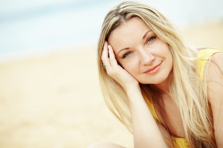 Middle aged woman resting at beach near the sea Stock Photo - 13151739