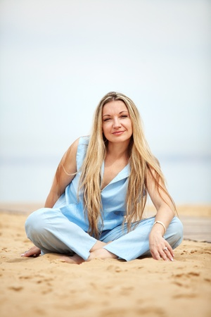 Middle aged woman resting at beach near the sea photo
