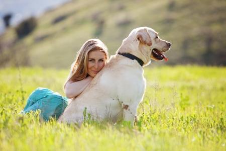 perros jugando: Mujer joven con perro ger descansando en el campo verde Foto de archivo