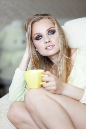 Bright portrait of beautiful woman with cup of tea sitting on the sofa photo
