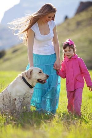 femme et chien: Happy family marche avec le chien dans le champ vert Banque d'images