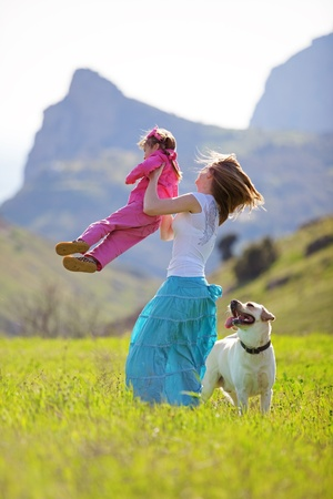 Happy family walking with dog in green field photo
