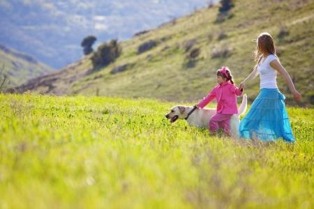 Familia feliz caminando con el perro en el campo verde
