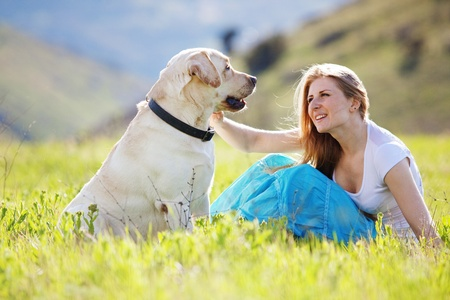 Young woman with ger dog resting at green field photo