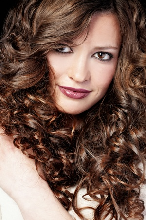 curly hair: Portrait of young beautiful woman with long curly volume hair