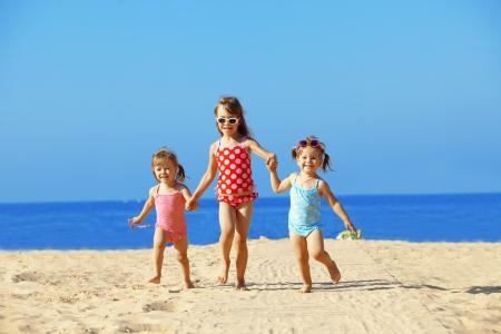 ni�o corriendo: Ni�os felices jugando en la playa en verano