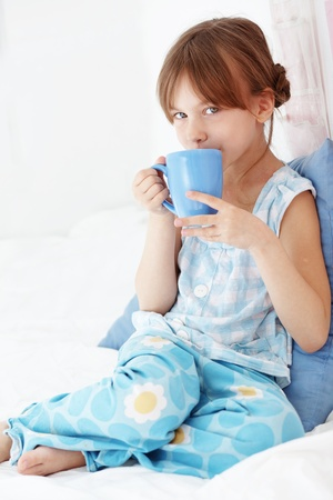 Home portrait of child drinking milk in bed photo