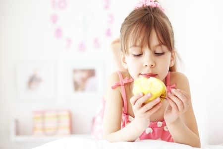 Casual portrait of cute child eating apple in bed photo