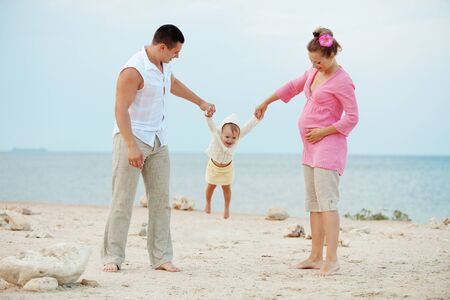 Portrait ofl young happy parents with child at the beach photo