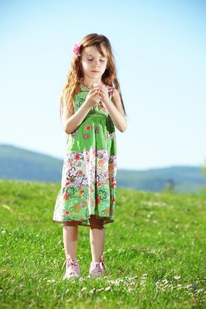 Cute kid girl at green field photo