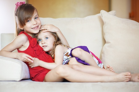 Two children resting on the sofa at home photo