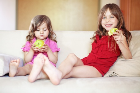 elementary age girl: Two children resting on the sofa at home