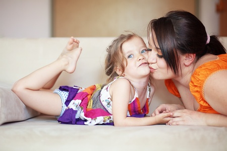 Mother with her small daughter playing on the sofa at home