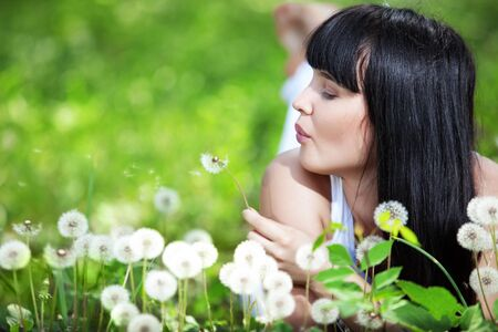 Young beautiful woman resting on fresh green grass photo