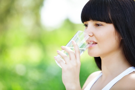Portrait of young woman drinking water at green park photo