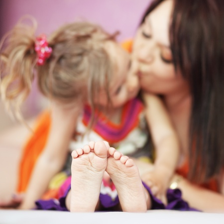 young girl feet: Mother with her small daughter playing on the sofa at home, focus on kids feet