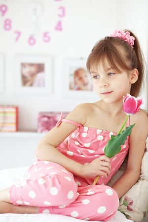 Photo of beuatiful kid girl with flower at home photo