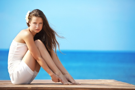 hot legs: Portrait of very beautiful young girl posing at the summer beach