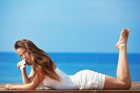 Retrato de niña Youg muy hermosa posando en la playa de verano