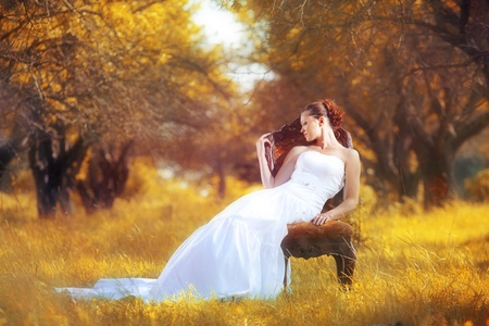 Portrait of beautiful bride sitting on the retro char at autumn forest photo