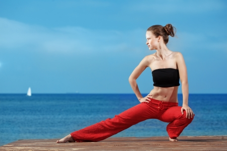 sport wear: Young beautiful woman doing fitness exercises at the beach Stock Photo