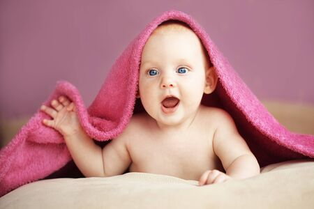 Picture of a baby lying under towel in bed photo