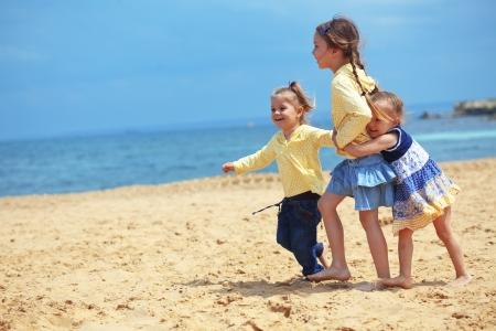 ropa de verano: Grupo de ni�os jugando en la playa Foto de archivo