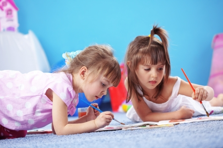 children playing with toys: Children drawing in the nursery